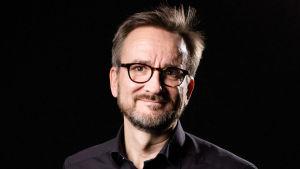 Vesa-Matti Lahti, glasögonprydd med skägg och svart skjorta stående framför en svart bakgrund.