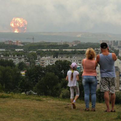 Ihmiset katsovat taivaanrannassa näkyvää räjähdystä.
