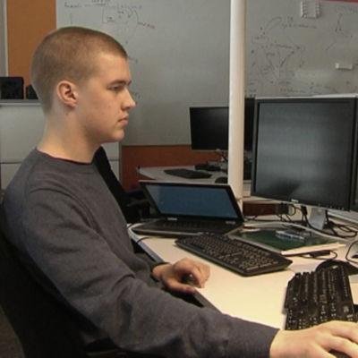 En ung man sitter vid sina dator.