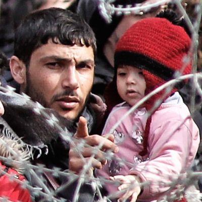 Joukko Kreikkaan pyrkiviä turvapaikanhakijoita seisoo piikkilanka-aidan takana. Kuvan keskellä on parrakas mies, joka pitelee sylissään pikkulasta ja osoittaa sormellaan kuvaajan suuntaan.*