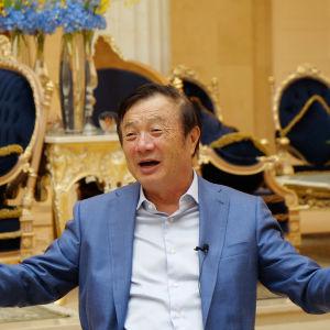 Ren Zhengfei, här iklädd blå kostym. I bakgrunden förgyllda stolar.