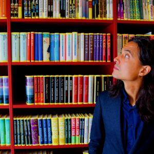 Jonas Hassen Khemiri står framför en bokhylla