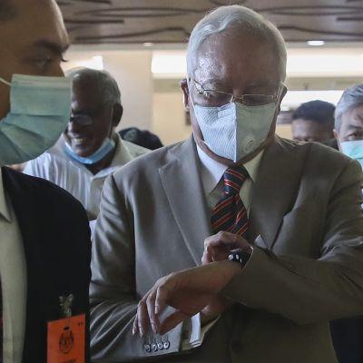 Najib Razak katsoo rannekelloaan maski kasvoillaan