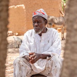 Mies istuu tuolissa kylän keskellä