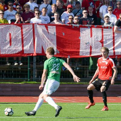 En bild på en fotbollsspelare i grönvitt (EIF) som sparkar på en boll. Bredvid honom finns spelare i rött och svart. Bakom fotbollsspelarna finns en banderoll där det står stadin kingit - de stöder laget i rött och vitt (HIFK)
