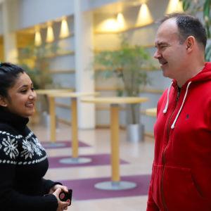 Elisha Baniya och Peter Vesterbacka, en dam med blå tröja och svart hår och en man med röd munkjacka.