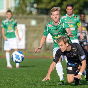 EN spelare är på knä och försöker nå bollen.