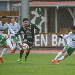 EN spelare skjuter iväg bollen och de andra försöker hindra honom.