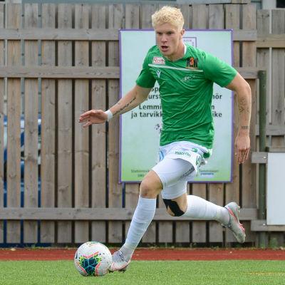 En fotbollsspelare springer med bollen i fötterna.