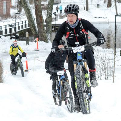 Tomi Paavola cyklar i vinterräng upp för en backe.