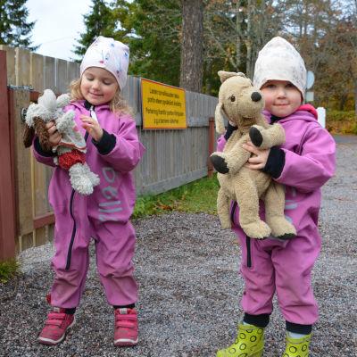 Två barn i rosa overaller står utomhus. De håller i var sitt gosedjur.