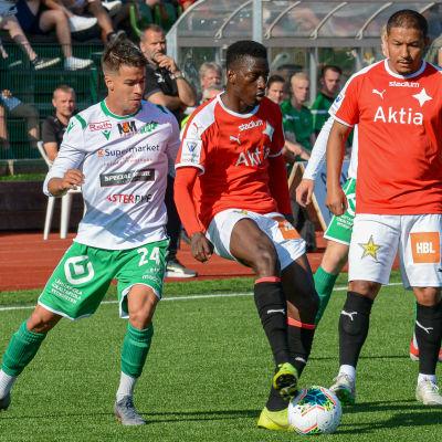 Tre spelare försöker nå bollen.