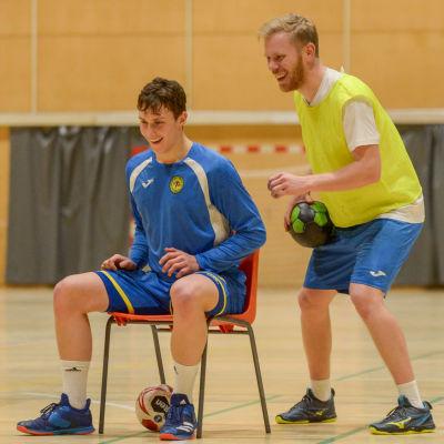 Mathias Sandblom och Robert Bäckman (sitter på stolen) har roligt på träningen.