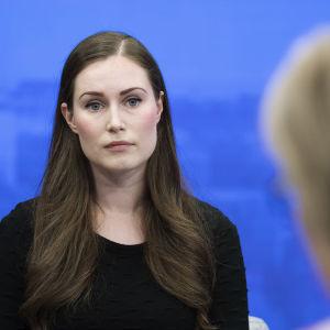 Sanna Marin mot en blå bakgrund i en tv-studio.