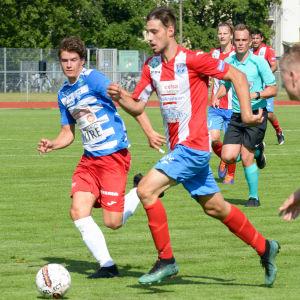 En fotbollsspelare springer med bollen i fötterna och jagas av andra spelare.