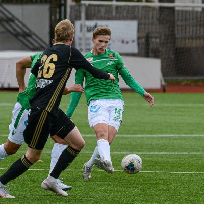 Simon Lindholm sparkar bollen omringad av fler SJK-spelare.