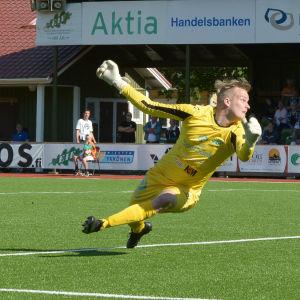 Fotbollsmålvakt kastar sig mot marken.