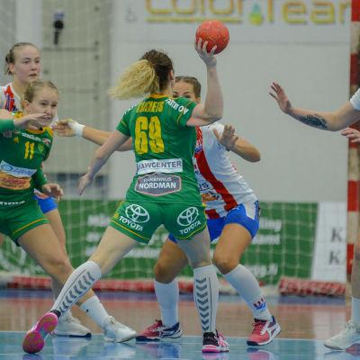 En spelare försöker skjuta bollen förbi försvarsmuren.