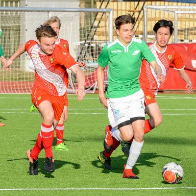 En fotbollsspelare springer med bollen i fötterna medan några spelare jagar honom.