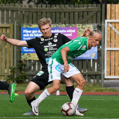 Akseli Ollila skyddar bollen framför en MUSa-spelare.