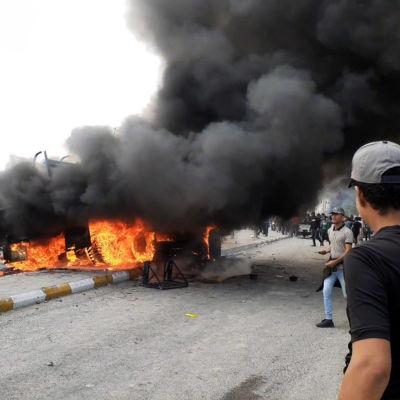 Demonstranter samlas kring ett brinnande militärfordon i Nasiriyah, Irak.