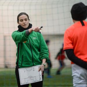 En kvinna gestikulerar framför ett par fotbollsjuniorer.