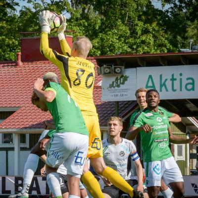 Fotbollsmålvakt greppar bollen framför näsan på andra spelare.