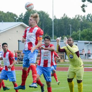 En spelare nickar bort en boll och många andra tittar på.