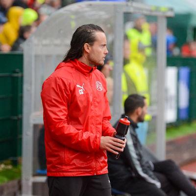 Christian Sund står med en vattenflaska i handen och tittar ut mot plan.