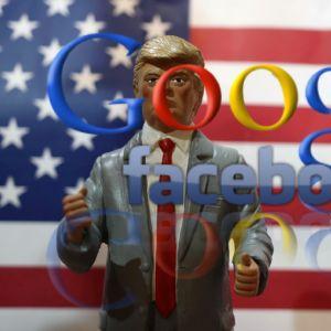 Trump- och Clinton-dockor med orden Google och Facebook framför dem.