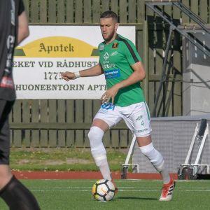 En fotbollspelare i grönvit mundering springer över gräsplan och sparkar mot en fotboll.