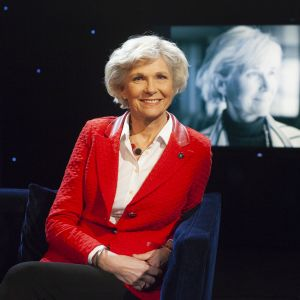 Pensionsbolagschefen Satu Huber sitter i Daniel Olins tv-studio i röd kavaj och vit blus.