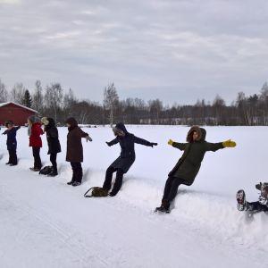 Noin kymmenen henkilöä seisoo lumisessa maisemassa tien reunassa, ja he oat kaatumassa taaksepäin selilleen pehmeään lumihankeen.