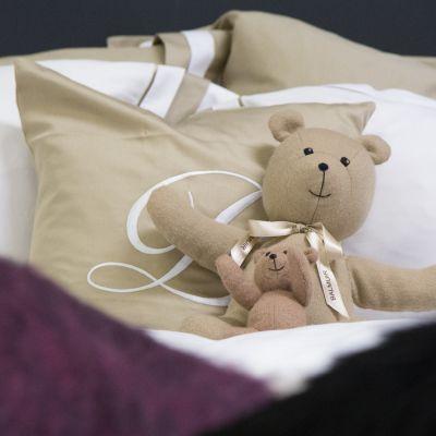 Nallet nojaavat tyynyyt pedatussa vuoteessa