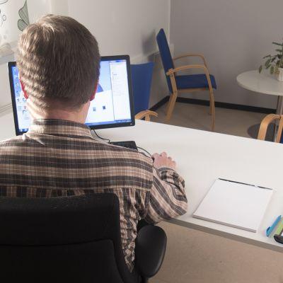 Sosiaalityöntekijä tietokoneen ääressä.