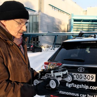 Emeritus professori Pasi Kuvaja esittelee &g tekniikalla toimivan auton pienoismallia.