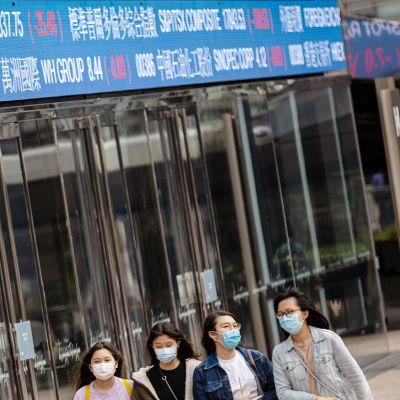 Suojamaskiin pukeutuneet nuoret kävelevät pörssikursseja näyttävän taulukon edustalla Hongkongissa.