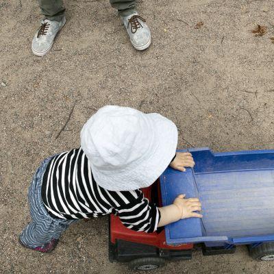 Lapsi leikkii kuorma-autolla leikkipuistossa.