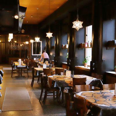 Työntekijä pyyhkii pöytää autiossa ravintolassa.