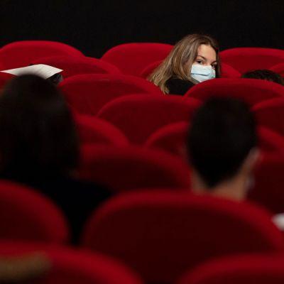 Kasvomaskiin pukeutunut asiakas elokuvateatterissa.