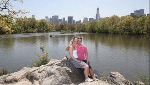 Christer Schoultz med fru på bröllopsresa poserar vid sjö med stadsvy i bakgrunden.