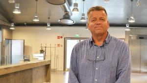 En medelålders man i kragskjorta står inne i Borgå Konstfabrik. Bakom honom syns taklampor och grå väggar.