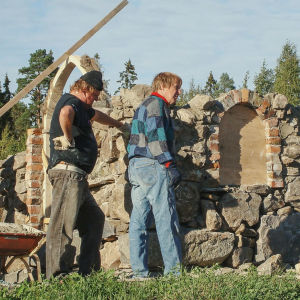Kaksi miestä rakenteilla olevan kirkon vieressä.