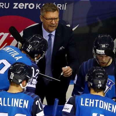 Jukka Jalonen pratar med landslagsspelare i båset under en match.