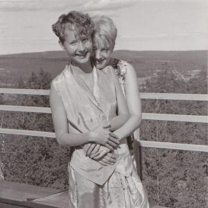 Mustavalkoinen kuva Tuula Juvosesta rakastamansa naisen kanssa näköalapaikalla.