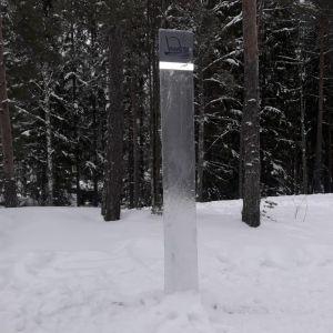 Kirkkaan metallin värinen monoliitti lumessa