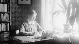 Miina Sillanpää arbetar vid sitt skrivbord.