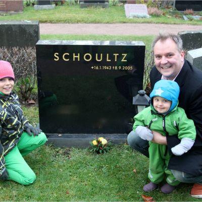 Christer Schoultz med sina barn vid pappas grav