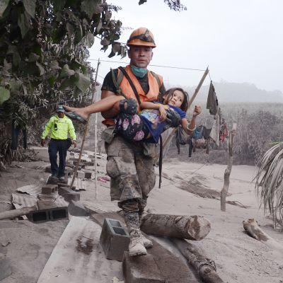 Pelastustiimin työntekijä kantoi tyttöä tulivuoren purkauksen jälkeen El Rodeossa, Guatemalassa 3. kesäkuuta.