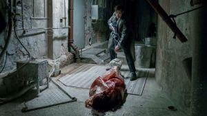 En man drar ett blodigt lik på golvet.